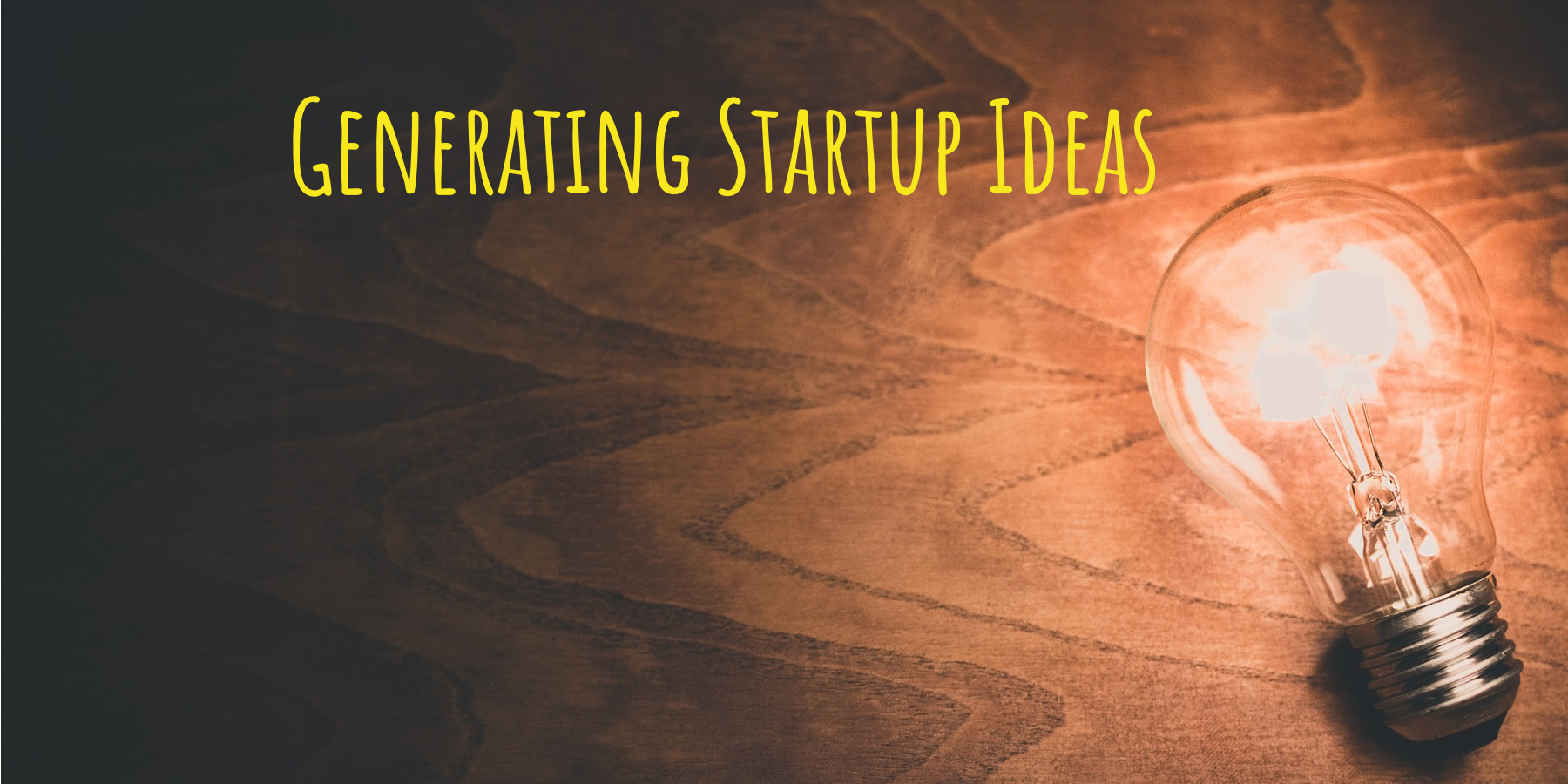 "lit up lightbulb on a wooden desk, with the words, ""generating startup ideas"" written over top"